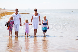 Family walking on the beach on a nice summer day.