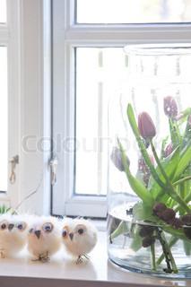 Lilla tulipaner i et stort glas og små påskekyllinger