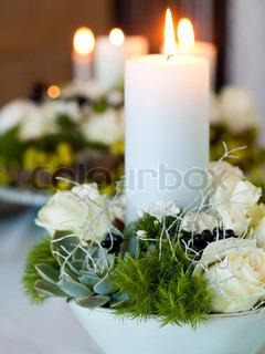 Fin juledekoration pyntet med tændte lys, blomster, mos og bær