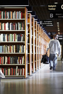 A male college student leaving the uiversity library