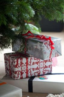 Julegaver stablet i en fin bunke under juletræet