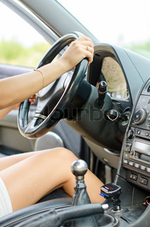 Woman's hand driving a car. Unrecognizable person.