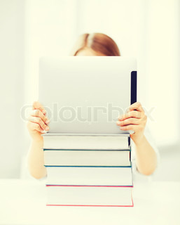 girl hiding behind tablet pc and books at school