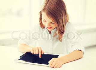smiling little girl with tablet pc at school