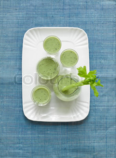 Aerial view of fresh green smoothies with celery stalk