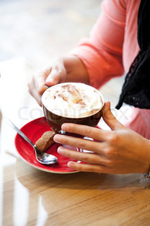 A woman drinking cappuccino in a cafe/restaurant