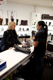 A saleswoman assistant a caucasian woman shopping for shoes