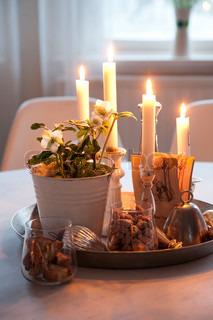 Et fint fad i sølv pyntet med brændende lys i stagger og blomster i krukken