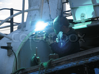 Welder repairing a fishing wessel.