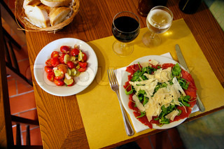 Italian lunch table with Carpaccio and tomato salad - bread - red wine and water. Natural lightening.