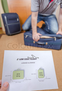 Man trying to close full hand luggage