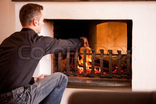 A caucasian man lighting a fireplace