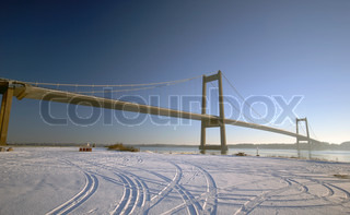 Tire tracks near suspension bridge.  Blue and cold snowy day in Denmark.