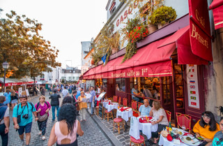 PARIS - JUNE 21, 2014: Tourists enjoy life in Montmartre narrow streets. Montmartre area is among most popular destinations in Paris, with its typical cafe and restaurants.