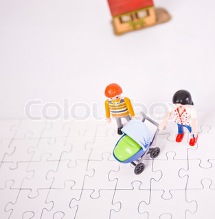 Concept of a young family standing over a puzzle board and a miniature house nearby