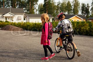 anxious 7 y girl heading for first day at school with empty backpack and her elder brother with bike anxious to get going