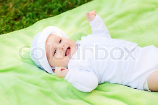 smiling baby lying on floor and looking up