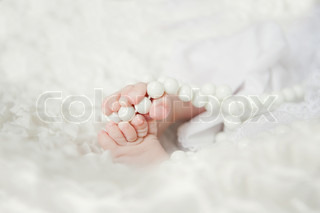 Small baby's feet with beads