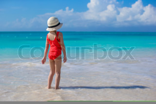 Little girl in hat at beach during caribbean vacation