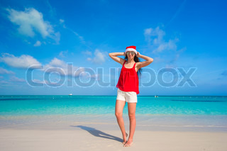 Beautiful young woman in santa hat on tropical beach