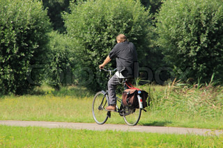 The solitary man cycling between willows go home in summertime.