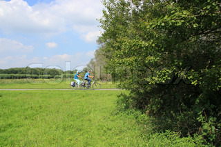Couple, man and wife, cycling between the bushes on the countryside and have a nice trip in summertime.