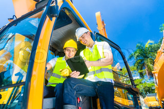 Asian construction driver discussing with engineer blueprints