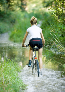 Rear view of a girl riding through water on bike