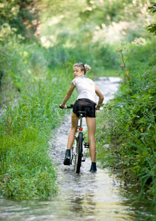 Portrait of a girl riding through wet path on bike amid foliage