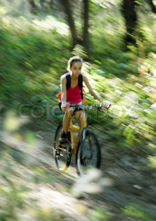 Blurred motion of a girl riding mountain bike downhill in forest