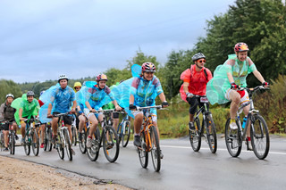 A group of cyclist racer racing  in the rain