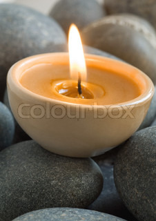 Close-up of lit candle on pebbles