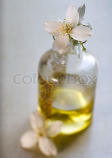 Mock orange flowers and bottle of massage oil