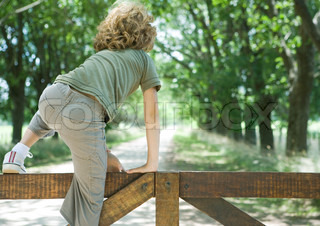 Rear view of a boy climbing on wooden gate