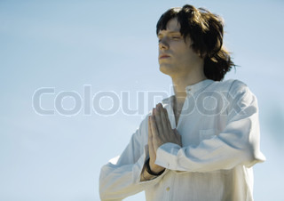 Young male meditator with hands clasped and eyes closed