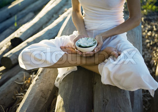 Woman sitting on pile of logs, holding bowl with lotus flower