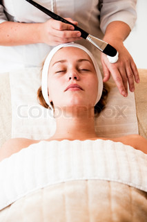 A female caucasian in a wellness spa getting facial treatment