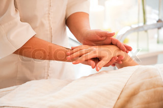 A female caucasian in a wellness spa getting hand massage