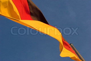 German flag waving in sunny wind on blue sky