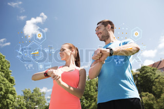 smiling couple with heart rate watches outdoors