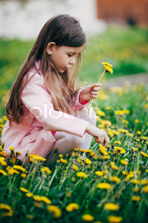 small girl sitting in flower field and feel happy