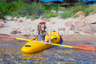 Little cute girl enjoy swimming on yellow kayak in clear turquoise water