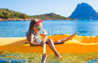 Little girl enjoying swimming in yellow kayak in the clear turquoise water