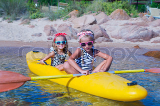 Little cute girls enjoying kayaking on yellow kayak in the clear turquoise water