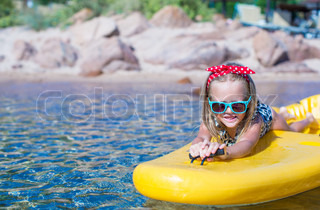 Little cute girl enjoying swimming on yellow kayak in the clear turquoise water