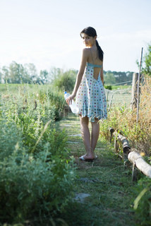 Portrait of a young woman standing in garden with bottle of water and looking over shoulder