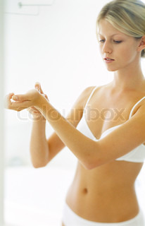Young woman in underclothes applying perfume