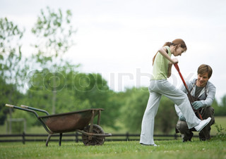 Girl digging in yard while man watches nearby