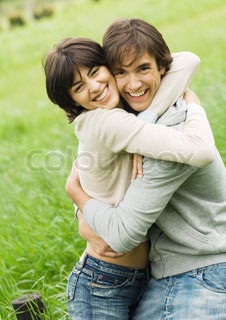 Portrait of young couple hugging and smiling