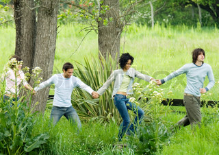 Group of young adult friends holding hands as they walk through park